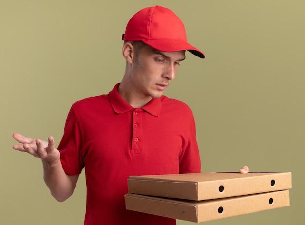 Il giovane ragazzo delle consegne biondo incapace tiene e guarda le scatole della pizza