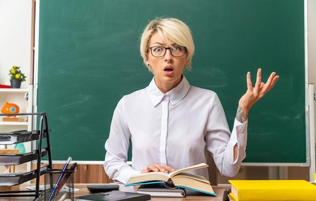 空の手を示しているカメラを見て開いた本に手を置いて教室で学校のツールと机に座って眼鏡をかけている無知な若いブロンドの女性教師