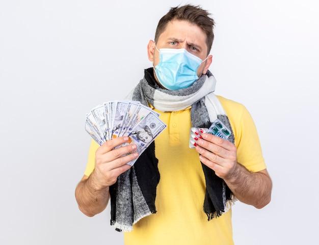 의료 마스크와 스카프를 착용하는 우 둔 젊은 금발의 아픈 남자는 돈과 흰 벽에 고립 된 의료 약의 팩을 보유