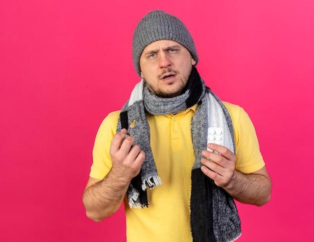 겨울 모자와 스카프를 착용하는 우둔한 젊은 금발의 아픈 슬라브 남자가 주사기를 보유하고 있습니다.