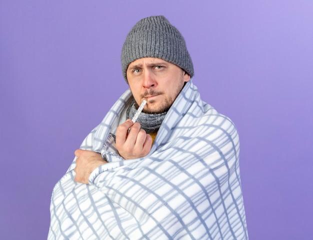 コピースペースと紫色の壁に分離された温度計で温度を測定する格子縞に包まれた冬の帽子とスカーフを身に着けている無知な若い金髪の病気のスラブ男