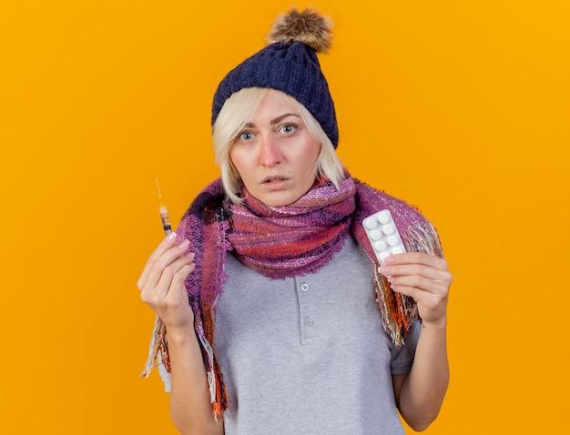 겨울 모자와 스카프를 착용하는 우 둔 젊은 금발의 아픈 슬라브 여자는 주사기를 보유