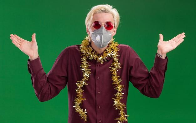 녹색 배경에 고립 된 빈 손을 보여주는 카메라를보고 목에 반짝이 갈 랜드와 안경과 보호 마스크를 쓰고 우 둔 젊은 금발의 남자