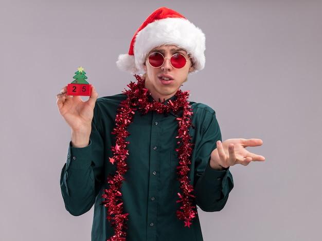 サンタの帽子と眼鏡をかけて首に見掛け倒しの花輪を身に着けている無知な若いブロンドの男は、白い背景で隔離の空の手を示してそれを見て日付とクリスマスツリーのおもちゃを保持しています