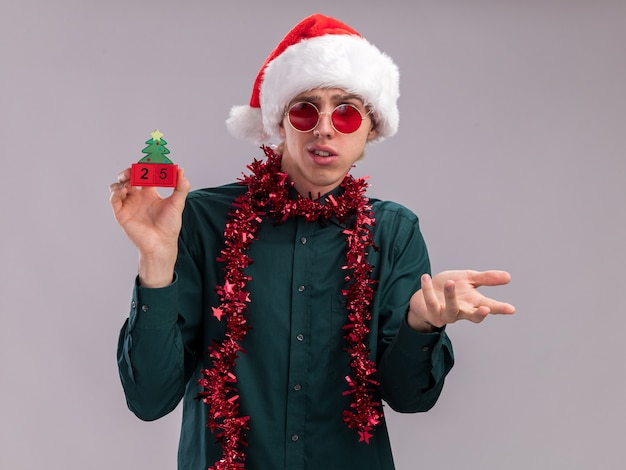 Clueless young blonde man wearing santa hat and glasses with tinsel garland around neck holding christmas tree toy with date looking at it showing empty hand isolated on white background