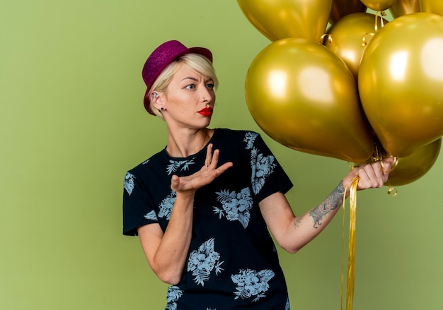 복사 공간 올리브 녹색 배경에 고립 된 풍선을보고 손으로 가리키는 파티 모자를 쓰고 우 둔 젊은 금발 파티 소녀