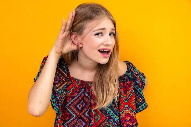 Невежественная молодая славянская блондинка держит руку рядом с ухом, пытаясь услышать
