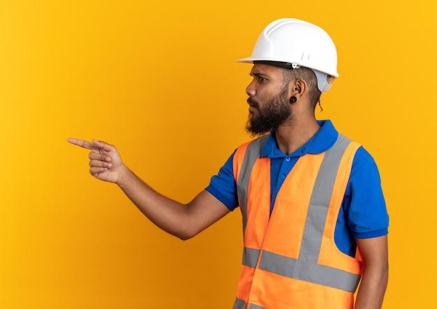 복사 공간이 있는 주황색 벽에 격리된 측면을 보고 가리키는 안전 헬멧을 쓴 제복을 입은 어리석은 젊은 건축업자