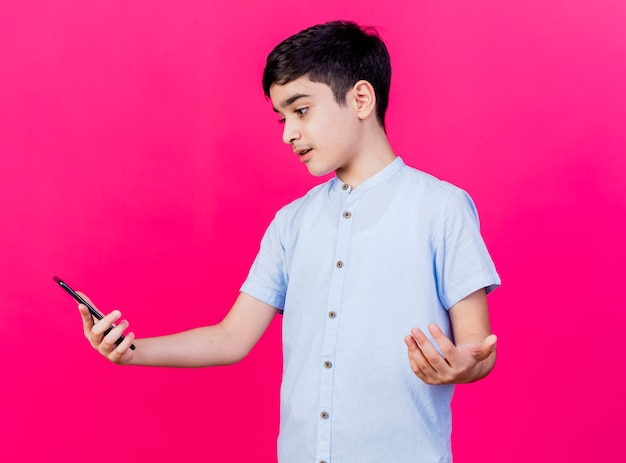 Clueless young caucasian boy holding and looking at mobile phone showing empty hand isolated on crimson background