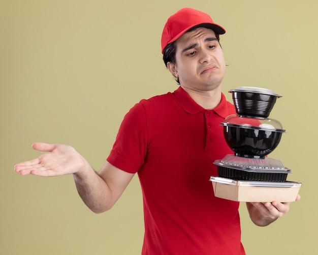 赤い制服を着た無知な若い白人配達人と帽子を持って食品容器と紙の食品パッケージを見て、オリーブグリーンの壁に隔離されたジェスチャーを知らない