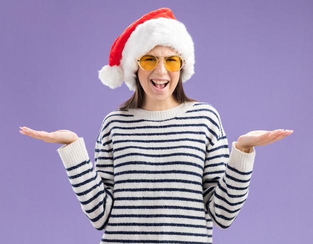 Ignara giovane ragazza caucasica in occhiali da sole con cappello da babbo natale che si tiene per mano aperta isolata sul muro viola con spazio di copia