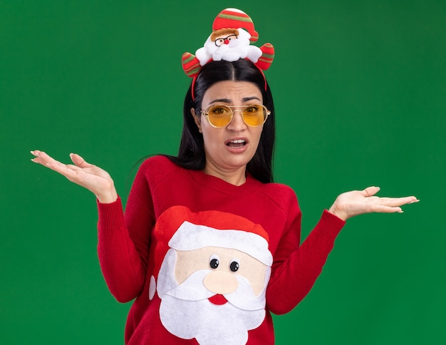 녹색 배경에 고립 된 빈 손을 보여주는 카메라를보고 안경 산타 클로스 머리띠와 스웨터를 입고 우 둔 젊은 백인 여자