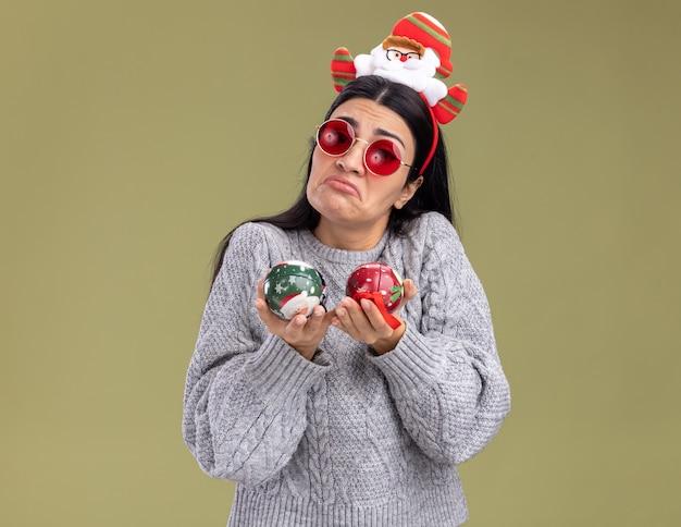 Clueless giovane ragazza caucasica indossando la fascia di babbo natale con gli occhiali che tengono le bagattelle di natale che guarda l'obbiettivo isolato su sfondo verde oliva