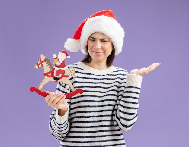 Clueless young caucasian girl with santa hat holding and looking at santa on rocking horse decoration