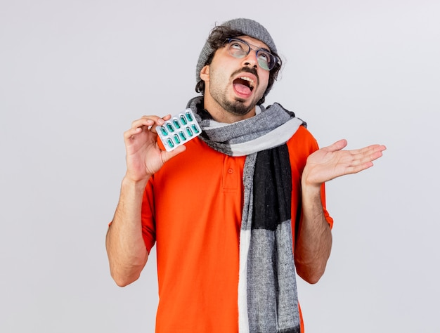 Clueless giovane indoeuropeo uomo malato con gli occhiali inverno cappello e sciarpa holding pack di capsule mediche cercando mostrando mano vuota isolata su sfondo bianco