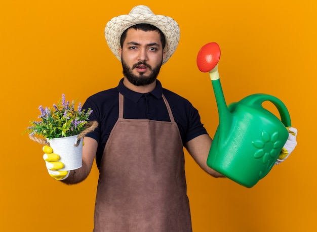 Clueless young caucasian male gardener wearing gardening hat and gloves holding flowerpot and watering can isolated on orange wall with copy space