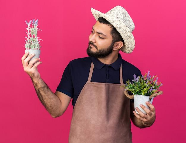 Giovane giardiniere maschio caucasico senza tracce che indossa cappello da giardinaggio che tiene vasi di fiori isolati sulla parete rosa con spazio di copia