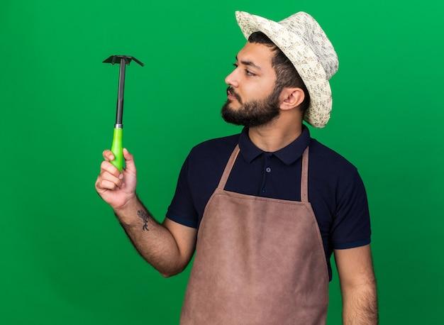 Giovane giardiniere maschio caucasico senza tracce che indossa cappello da giardinaggio tenendo e guardando il rastrello della zappa isolato sulla parete verde con spazio di copia