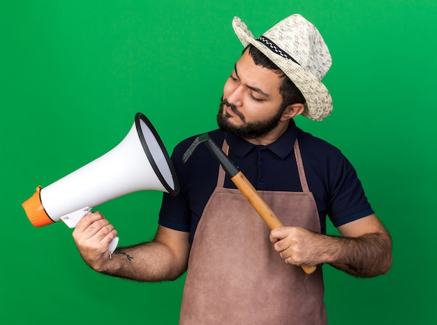 熊手を保持し、コピースペースで緑の壁に分離された大音量のスピーカーを見ている園芸帽子をかぶっている無知な若い白人男性の庭師