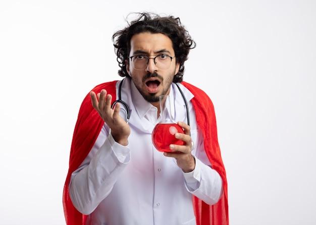 赤いマントと聴診器を首にかけた医者の制服を着た光学ガラスの無知な若い白人男性は、手を上げて立って、ガラスフラスコに赤い化学液体を保持します