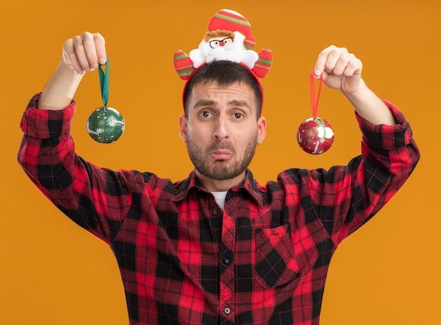 Невежественный молодой кавказский мужчина в повязке на голову санта-клауса смотрит в камеру с рождественскими шарами, изолированными на оранжевом фоне