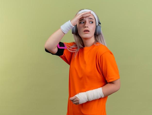 머리띠 팔찌와 전화 완장을 착용하는 헤드폰에 중괄호가있는 우 둔 젊은 백인 스포티 한 소녀는 올리브 녹색 벽에 고립 된 측면을보고 이마에 손바닥을 옆으로 유지합니다.