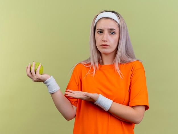Невежественная молодая кавказская спортивная девушка с подтяжками, носящая повязку на голову и браслеты, держит и указывает на яблоко