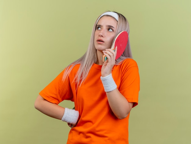 Clueless giovane caucasica ragazza sportiva con bretelle che indossa archetto e braccialetti contiene racchette da ping-pong guardando a lato