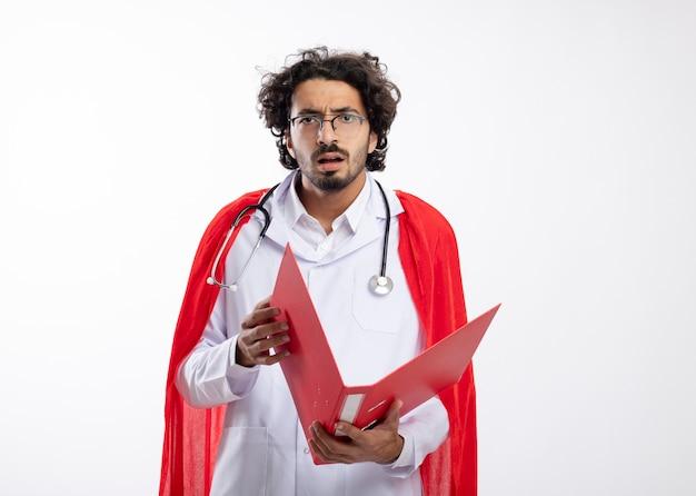 Ignaro giovane supereroe caucasico uomo in occhiali ottici che indossa l'uniforme del medico con mantello rosso e con uno stetoscopio intorno al collo tiene la cartella