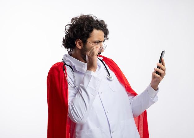 Ignaro giovane supereroe caucasico uomo in occhiali ottici che indossa l'uniforme da medico con mantello rosso e con lo stetoscopio intorno al collo tiene e guarda il telefono