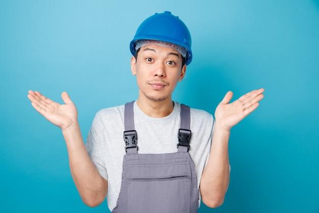 安全ヘルメットと空の手を示す制服を着た無知な若い建設労働者