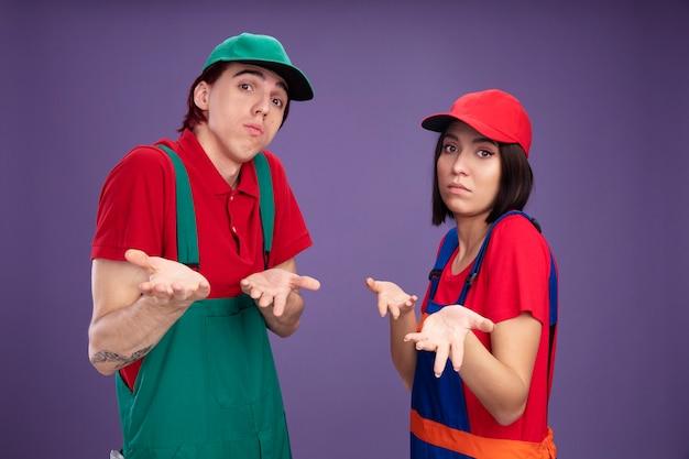 Giovani coppie incapaci in uniforme da operaio edile e cappuccio in piedi nella vista di profilo che mostra le mani vuote