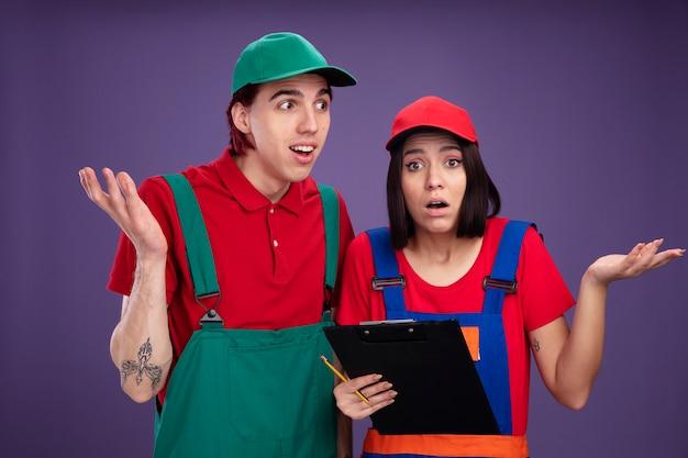 建設労働者の制服を着た無知な若いカップルと鉛筆とクリップボードを持っているキャップの女の子は両方とも紫色の壁に隔離されたカメラを見ている側の女の子を見ている空の手の男を示しています