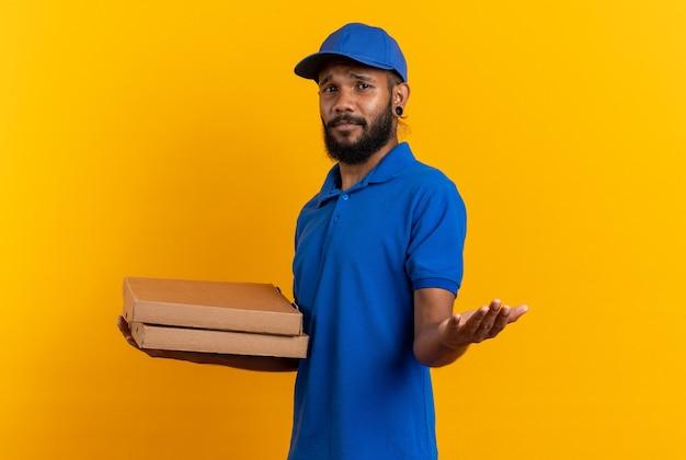 ピザの箱を持って、コピースペースでオレンジ色の壁に隔離された正面を指している無知な若い配達人