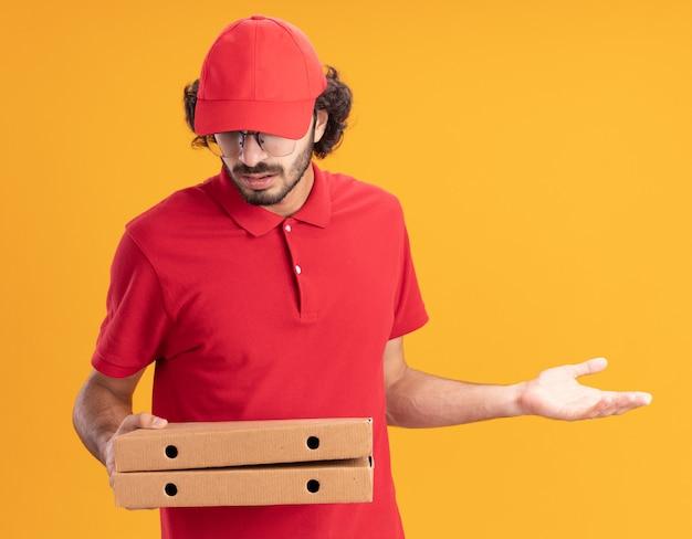 オレンジ色の壁に隔離された空の手を示すピザのパッケージを保持し、見て眼鏡をかけている赤い制服と帽子の無知な若い配達人