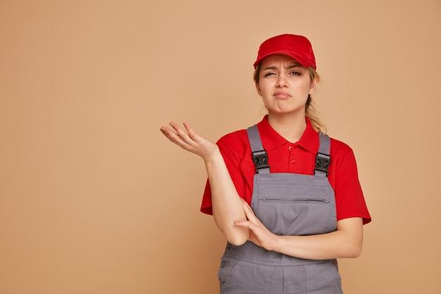 空の手を示すキャップと制服を着た無知な若い女性の建設労働者