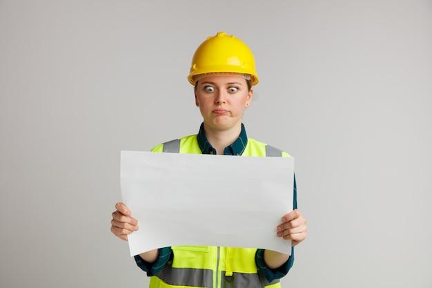 安全ヘルメットと安全ベストを身に着けている無知な若い女性の建設労働者は、口すぼめ呼吸で紙を保持し、見ています