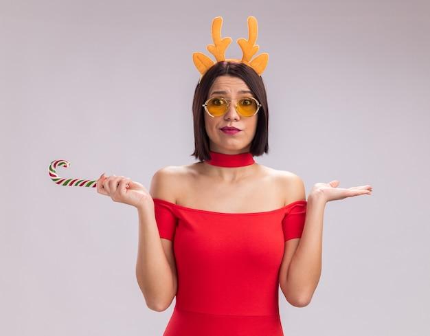 トナカイの角のヘッドバンドと白い背景で隔離のカメラを見て空の手を示すクリスマスクリスマスキャンディケインを保持しているメガネを身に着けている無知な少女