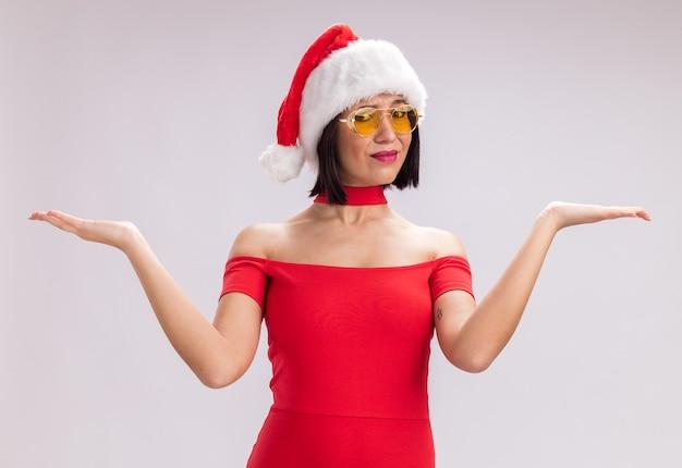 Невежественная молодая девушка в шляпе санта-клауса и очках смотрит в камеру, показывая пустые руки, изолированные на белом фоне
