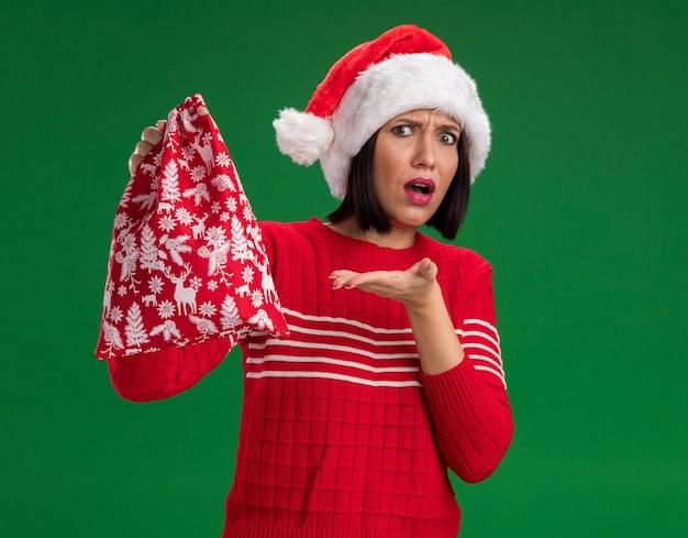 Бестолковая молодая девушка в шляпе санта-клауса держит и показывает на рождественский подарочный мешок, изолированное на зеленой стене