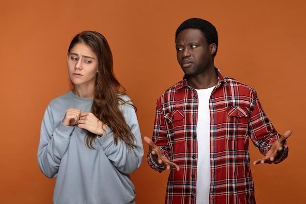困惑した表情でガールフレンドを見て、迷子になっているアフリカ民族の無知な青年は、彼女をまったく理解できません。彼氏に不満を感じている不確かな白人女性