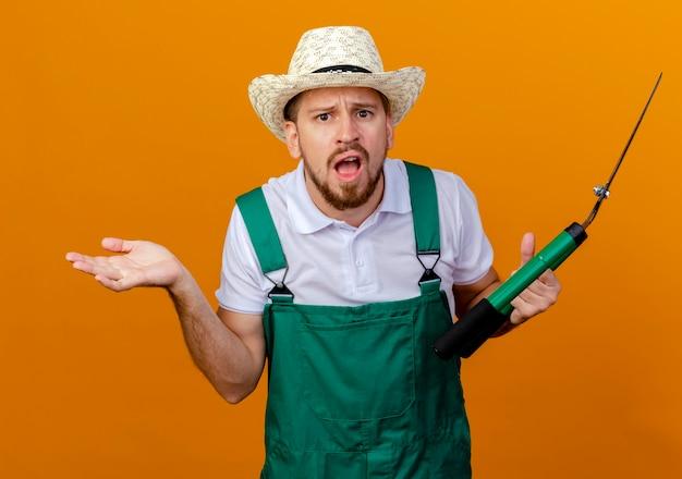 制服を着た無知な若いハンサムなスラブの庭師と帽子をかぶったプルーナーが孤立しているように見える空の手を示しています 無料写真