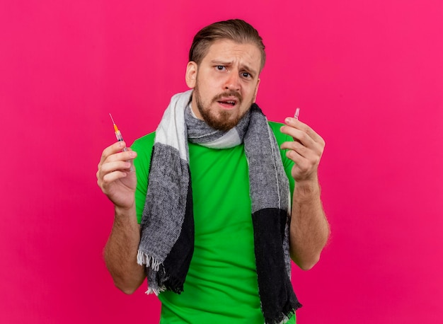 Clueless young handsome slavic ill man wearing scarf holding syringe and ampoule looking at front isolated on pink wall with copy space