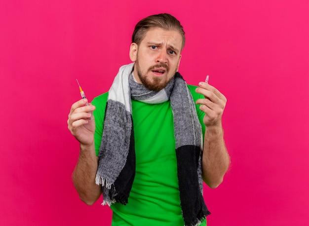 コピースペースでピンクの壁に隔離された正面を見て注射器とアンプルを保持しているスカーフを身に着けている無知な若いハンサムなスラブの病気の男
