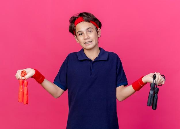真っ赤な背景に分離された縄跳びを保持しているカメラを見て歯科ブレースとヘッドバンドとリストバンドを身に着けている無知な若いハンサムなスポーティな少年
