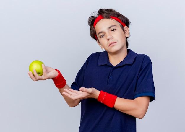 Giovane ragazzo sportivo bello all'oscuro che indossa la fascia e i braccialetti con le parentesi graffe dentali che tengono e che indica con la mano alla mela isolata sulla parete bianca
