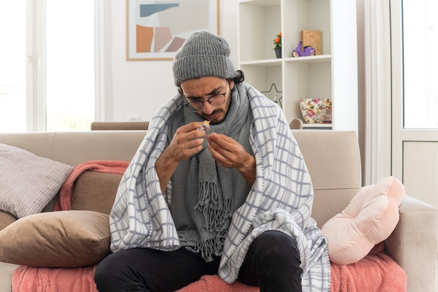 Giovane uomo malato senza tracce in occhiali ottici avvolto in plaid con sciarpa intorno al collo che indossa cappello invernale che tiene e guarda l'ampolla medica e la siringa seduto sul divano in soggiorno