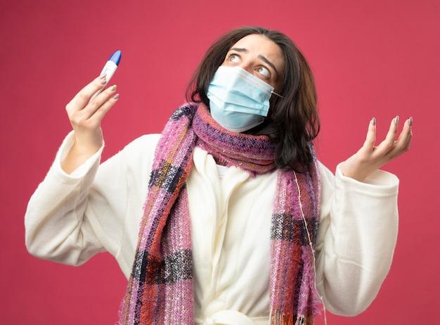 Clueless giovane donna malata che indossa accappatoio e sciarpa con maschera che tiene il termometro che mostra la mano vuota che osserva in su isolato sulla parete rosa