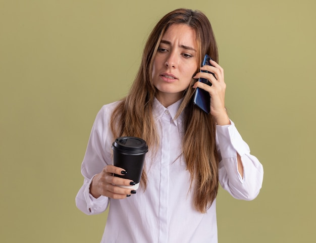 Clueless young pretty caucasian girl holds paper cup and talks on phone
