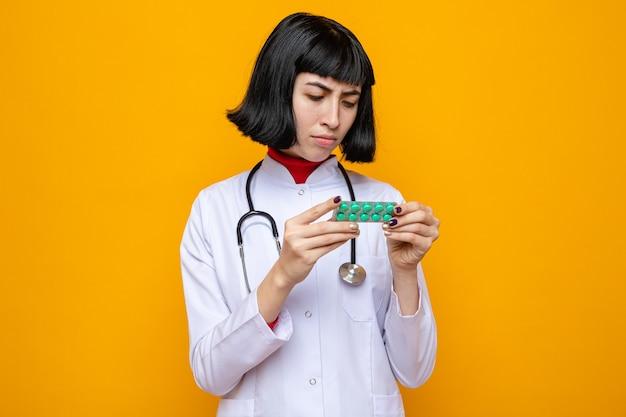 Бестолковая молодая симпатичная кавказская девушка в униформе врача со стетоскопом держит и смотрит на упаковку таблеток